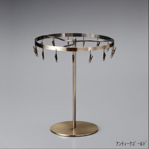 ●商品名:チーフ・ハンカチスタンド 回転式  ●表面処理:アンティークゴールドメッキ(AG)仕上 ●寸法:高さ300mm 上部回転リング直径240mm  ●上部回転式リング:クリップ15個付   ●材質:スチール ●特長:百貨店様では棚板高さのスパンが30cm強の設定が多いと教えてもらい、では「高さ30cmのスペースにフィットするチーフツリーを作ろう」ということで高さ30cmのチーフツリーを製造しました。また、クリップの先端には塩ビのキャップを装着し、展示商品を傷つけにくい仕上がりになっています。 ●生産国:日本(タヤ自社工場)