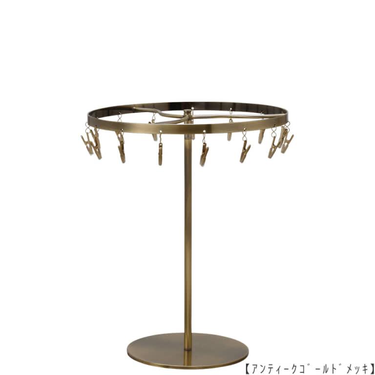 ●商品名:チーフ・ハンカチスタンド 回転式  ●表面処理:アンティークゴールド(AG)仕上 ●寸法:高さ300mm 上部回転リング直径240mm  ●上部回転式リング:クリップ15個付   ●材質:スチール ●特長:百貨店様では棚板高さのスパンが30cm強の設定が多いと教えてもらい、 では「高さ30cmのスペースにフィットするチーフツリーを作ろう」ということで高さ30cmのチーフツリーを製造しました。 また、クリップの先端には塩ビのキャップを装着し、展示商品を傷つけにくい仕上がりになっています。 ●生産国:日本(タヤ自社工場)
