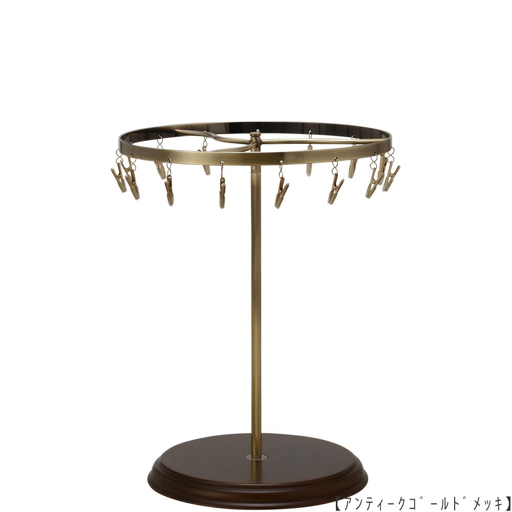 ●商品名:チーフ・ハンカチスタンド回転式 木製ベース仕様  ●表面処理:アンティークゴールド(AG)仕上 ●寸法:高さ315mm 上部回転リング直径240mm  ●上部回転式リング:クリップ15個付   ●材質:スチール ●特長:クリップの先端には塩ビのキャップを装着し、展示商品を傷つけにくい仕上がりになっています。さらに、木製のベースを組み合わせることで、落ち着きのある存在感と高級感を演出できます。 ●生産国:日本(タヤ自社工場)