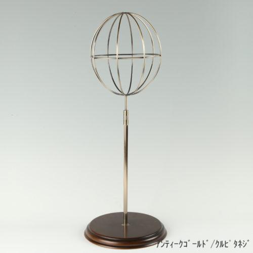 ●商品名:帽子スタンド 球体型-M ローレットネジ・木製ベース仕様 ●表面処理:アンティークゴールドメッキ(AG)仕上 ●寸法:高さ495~605mm ●ヘッド部:ワイヤー製ラグビーボール型球体ヘッド ●ヘッド:上下可動式(伸縮式) ●材質:スチール・木製(ベース) ●特長:抜け感がおしゃれなワイヤーヘッドに木製ベースを組み合わせ、落ち着きのある存在感と高級感を演出するツール ●生産国:日本(タヤ自社工場)