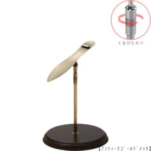 ●商品名:シューズスタンド片足用 くるぴたネジ・木製ベース仕様 ●表面処理:アンティークゴールド(AG)仕上 ●寸法:高さ260~360mm  ●ヘッド部:傾斜角度調整機能付。靴滑り落ち防止部材溶接留。 ●ヘッド:上下可動式(伸縮式) ●材質:スチール ●特長:展示物である靴のデザインを際立たせる天板デザイン設計。 天板を足型状にすることにより、靴を乗せると天板が隠れるサイズで製造。 天板が見えなくなる事によりお客様の視線が展示物の靴に集中、靴のデザインが際立ちます。 ●片足用スタンドである理由:両足分の靴をセットで展示しておくと、 靴を持って行かれてしまう可能性が高くなるとのお話を聞き、 通常品としては片足用のシューズスタンドをご用意しました。 また、木製のベースを組み合わせることで、落ち着きのある存在感と高級感を演出できます。 ●生産国:日本(タヤ自社工場)