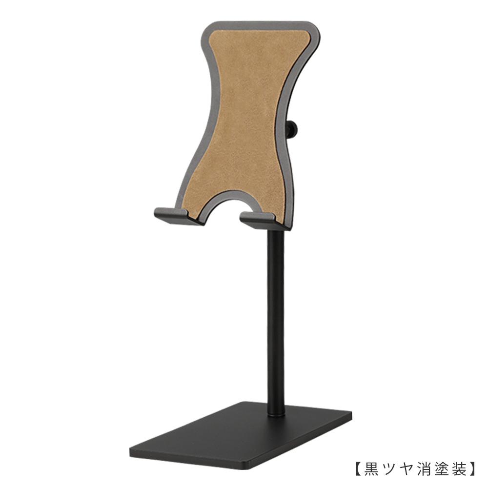 ●商品名:スマホスタンド 中  ●型番:SPS-01-S-MO16-BK-M  ●表面処理:黒ツヤ消塗装  ●素材:鉄  ●特長:素材である鉄の特徴を活かし、「スタイリッシュ」「省スペース」「機能性」を兼ね備えたデザインを目指し設計。ベース(鉄板の台座)には必要最低限の面積と重量を持たせ安定感を確保。スマートフォンを置いたり取ったりする際にスタンドごとスマートフォンを持ちあげてしまわないよう、ヘッド部天板両サイドには緩やかな曲線のクボミをつけ指がかかりにくくなるよう配慮したデザイン。  ベースの裏面とスマートフォンが接する天板部分にはそれぞれ形状に合わせたフェルトのシートが貼られ、デスクやスマートフォンに傷がつきにくい仕様。  ヘッド部は「角度」「高さ」の調整が可能、「回転」させることもできます。スマートフォンスタンドを使用する目的に合わせ、お好みの「角度」や「高さ」「向き」に調整し快適なスマートフォンタイムをお楽しみください。  また、ケーブルをスマホに差したままスタンドが使用できる仕様となっていますので充電しながらのご使用、ヘッドホンを使用しながらのご使用も可能です。   ●ヘッド上下調節・向きの調整: ローレットネジを締めることにより固定します(指でネジを回せる仕様です)。  ●ヘッド角度調整: 力で角度調整ができるようになっています。お好みの力で角度が変わるように調整する際には同梱の六角レンチを使用してお好みの硬さに調整してください。   ●日本製