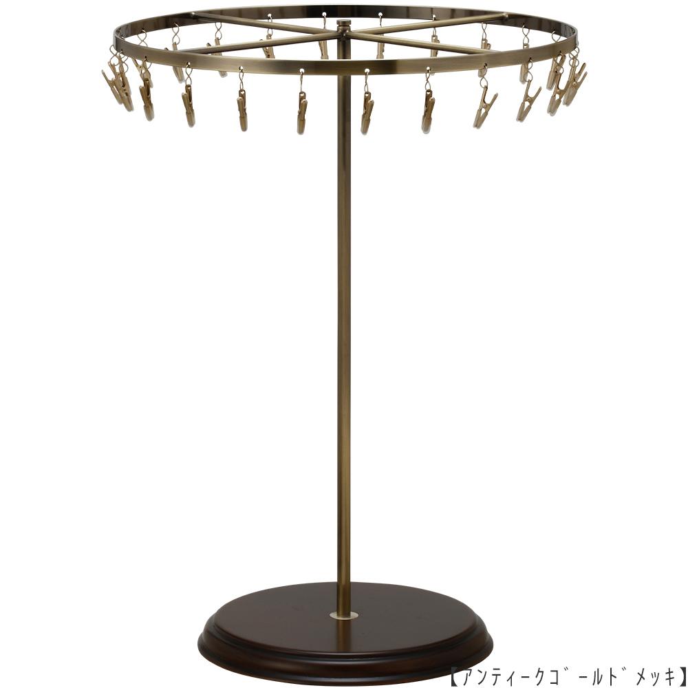●商品名:チーフ・ハンカチスタンド回転式 Lサイズ 木製ベース仕様  ●表面処理:アンティークゴールド(AG)仕上 ●寸法:高さ420mm 上部回転リング直径300mm  ●上部回転式リング:クリップ24個付   ●材質:スチール・ ●特長:長さのある小物も吊り下げることができるように、高さを付けました。小物を吊るす円形部分は、見やすいように回転させることが可能です。 クリップの先端には塩ビのキャップを装着し、展示商品を傷つけにくい仕上がりになっています。さらに、木製のベースを組み合わせることで、落ち着きのある存在感と高級感を演出できます。 ●生産国:日本(タヤ自社工場)